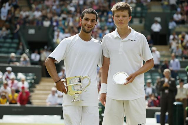 Noah Rubin of the U.S., left, holds the trophy after defeating Stefan Kozlov of the U.S., right, in the boys' singles final at the All England Lawn Tennis Championships in Wimbledon, London, Sunday July 6, 2014. (AP Photo/Alastair Grant)