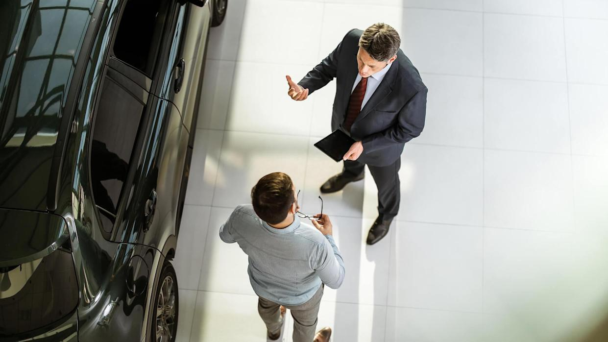 High angle view of a salesperson using touchpad while talking to his male customer in a car showroom.
