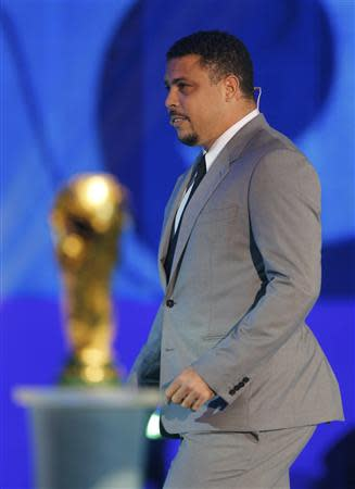 Former Brazill soccer player Ronaldo walks past by the World Cup trophy on stage during the draw for the 2014 World Cup at the Costa do Sauipe resort in Sao Joao da Mata, Bahia state, December 6, 2013. REUTERS/Paulo Whitaker