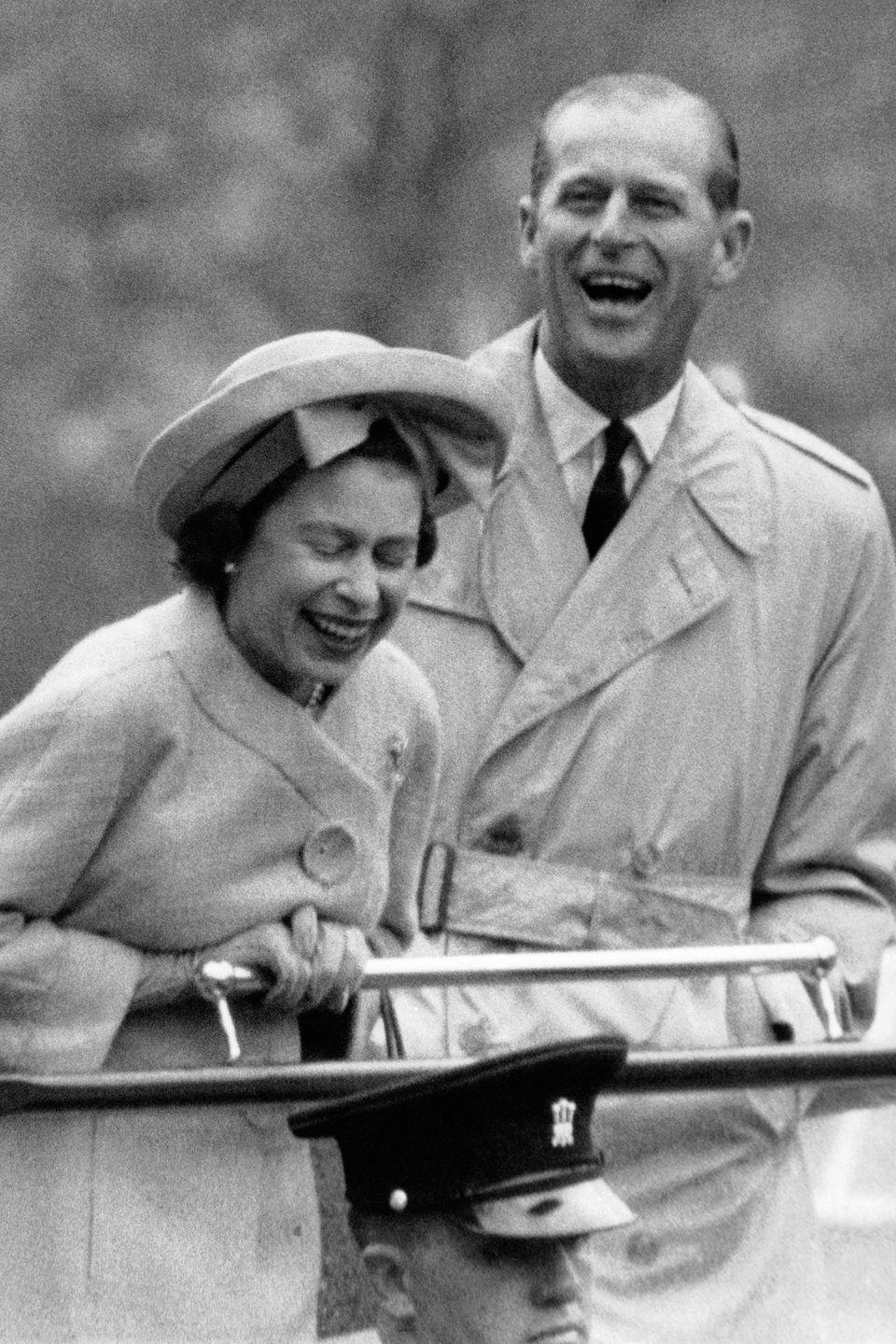 <p>Queen Elizabeth and Prince Philip share a laugh while watching a rope acrobat performed by two young recruits during their visit to a military camp in Wales in the spring of 1963. </p>