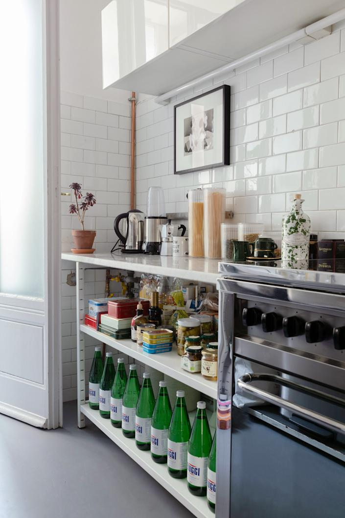 """<div class=""""caption""""> The apartment came equipped with a gas stove by <a href=""""https://www.lofra.it/en/"""" rel=""""nofollow noopener"""" target=""""_blank"""" data-ylk=""""slk:Lofra"""" class=""""link rapid-noclick-resp"""">Lofra</a> and white industrial shelving topped by a marble worktop. </div>"""