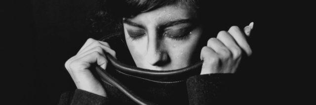 black and white photo of woman with eyes closed and pulling scarf up to cover her mouth