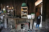 Orlando Chavez walks through his kitchen after performing back-breaking work collecting African palm bunches, in El Progreso, Honduras