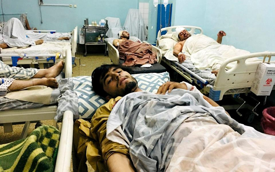 Wounded Afghans lie on a bed at a hospital after a deadly explosions outside the airport in Kabul, Afghanistan - AP