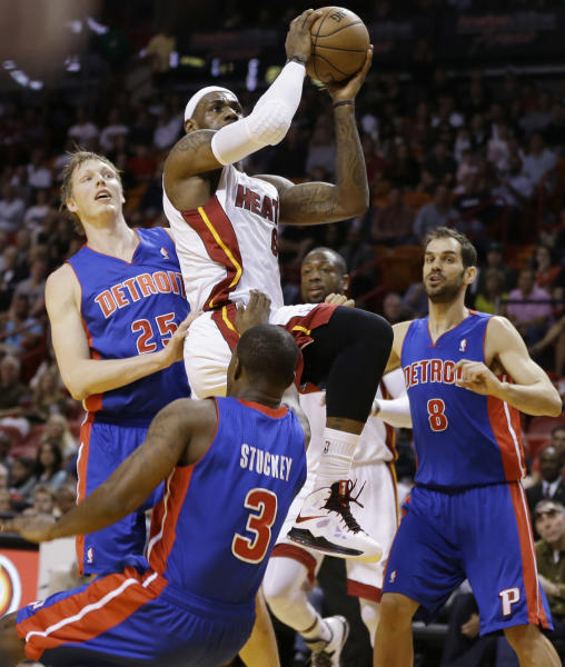 Miami Heat's LeBron James (6) goes between Detroit Pistons players Kyle Singler (25), Jose Calderon (8) and Rodney Stuckey (3) for a two point shot during the first half of a NBA basketball game in Miami, Friday, March 22, 2013. (AP Photo/J Pat Carter)