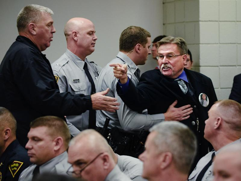 """Sheriff's deputies escort Al Lowry, the brother of murdered Highway Patrol Trooper, Ed Lowry after he yelled an expletive at Cumberland County Superior Court Judge Gregory A. Weeks, Thursday, Dec. 13, 2012 in Fayetteville, N.C. Judge Weeks declared the death sentences commuted to life without parole under the Racial Justice Act for Lowry's brother's killer, Tilmon Golphin. Defendants Christina S. """"Queen"""" Walters, and Quintel M. Augustine sentences were also commuted to life without parole. (AP Photo/The Fayetteville Observer, Raul R. Rubiera) MANDATORY CREDIT"""