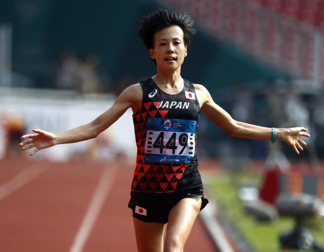 Japan's Keiko Nogami reacts as she crosses the finish line in second place in the women's marathon during the athletics competition at the 18th Asian Games in Jakarta, Indonesia, Sunday, Aug. 26, 2018. (AP Photo/Bernat Armangue)