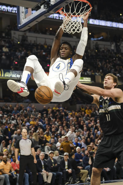 Indiana Pacers guard Victor Oladipo (4) dunks in front of Milwaukee Bucks center Brook Lopez (11) during the first half of an NBA basketball game in Indianapolis, Wednesday, Feb. 12, 2020. (AP Photo/AJ Mast)