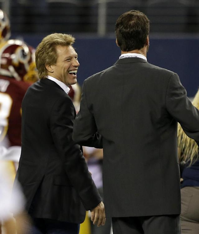 Singer Jon Bon Jovi, left, talks with broadcast personality Babe Laufenberg, right, as the teams warm up before an NFL football game between the Washington Redskins and Dallas Cowboys, Sunday, Oct. 13, 2013, in Arlington, Texas. (AP Photo/LM Otero)