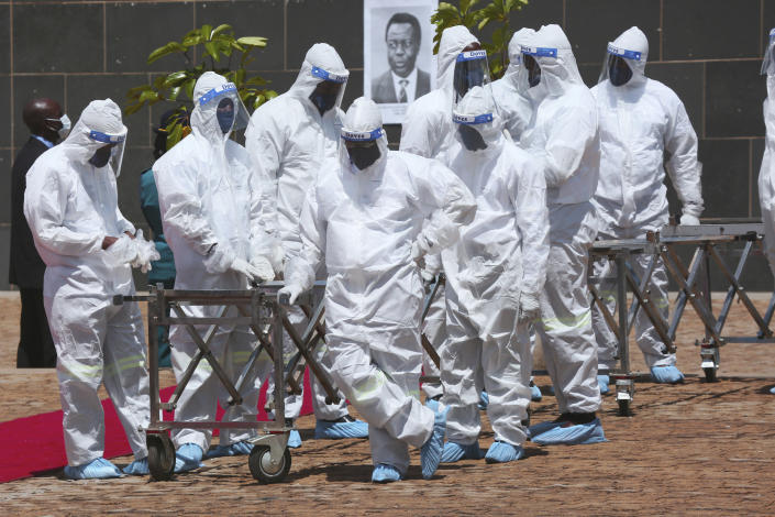 """Pallbearers wait for the coffins to arrive at a state burial of government ministers who died of COVID-19, in Harare, Thursday, Jan. 21, 2021. Zimbabwean President Emmerson Mnangagwa who presided over the burial called the pandemic """"evil"""" and urged people to wear masks, practice social distancing and sanitize, as cases across the country increased amid a fragile health system. (AP Photo/Tsvangirayi Mukwazhi)"""
