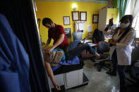 """A sex worker who fainted from not eating enough on the stairwell outside the offices of Brigada Callejera or """"The Street Brigade"""", is treated by Dr. Geovanna Alva, right, assisted by a nurse, inside the organization's treatment room in Mexico City, Friday, March 5, 2021. """"The Street Brigade"""" advocates for recognition and respect for Mexico's sex workers, offers them discount medical care, leftover prescription drugs and provides free classes including basic literacy, high school equivalency, and nursing skills. (AP Photo/Rebecca Blackwell)"""