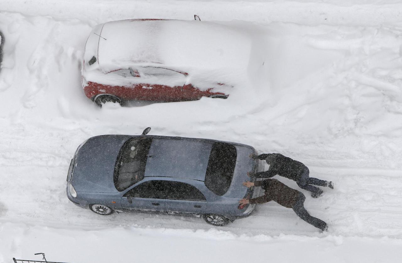 People push a car under snowfall in Kiev, Ukraine, Saturday, March 23, 2013. Heavy snow storms from the Balkan region have been stricken Ukraine since Friday. (AP Photo/Efrem Lukatsky)