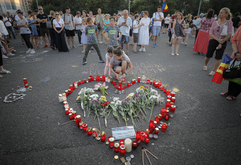 People light candles outside the government headquarters in memory of a 15 year-old girl, raped an killed in southern Romania, after police took 19 hours from the moment she called the country's emergency hotline to intervene, in Bucharest, Romania, Saturday, July 27, 2019. Thousands of people took part Saturday evening in Bucharest in a march protesting the handling of the case, blaming Romanian officials for negligence, incompetence and a lack of empathy. (AP Photo/Vadim Ghirda)