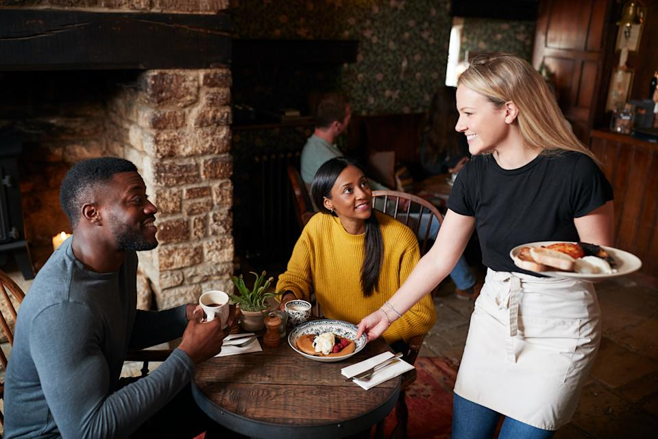 Waitress Working In Traditional English Pub Serving Breakfast To Guests