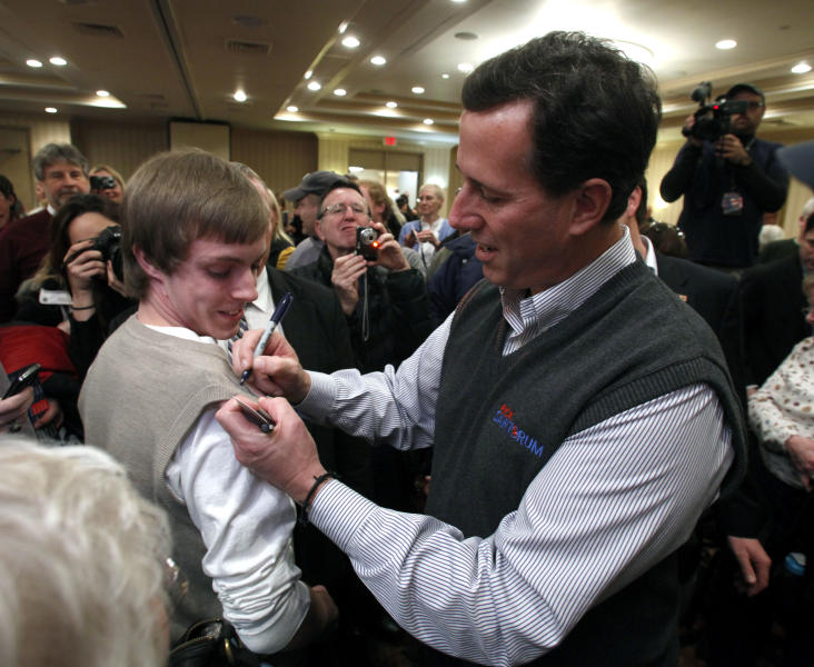 Republican presidential candidate, former Pennsylvania Sen. Rick Santorum, right, signs the sweater of Robert Casler, 17, of Muskegon, following a rally, Monday, Feb. 20, 2012, in Muskegon, Mich. (AP Photo/Al Goldis)