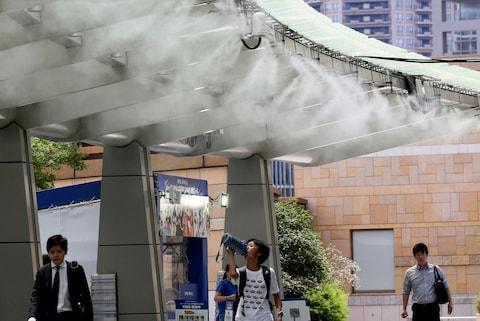 Water spray cools passers-by in Toky - Credit: AP Photo/Koji Sasahara
