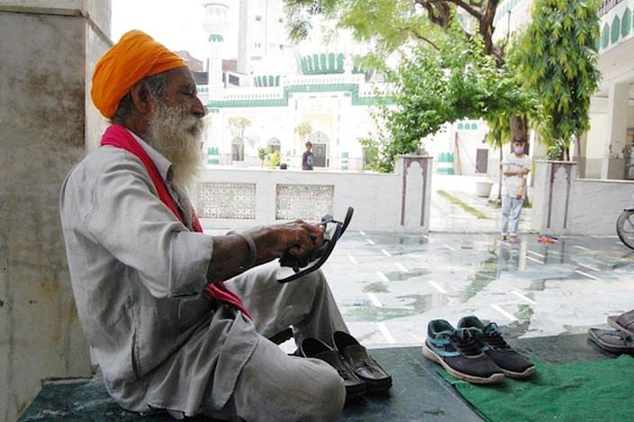 Baljinder Singh, 60, cleans shoes of devotees visiting the Khairuddin Mosque as a voluntary service, at Hall Bazaar, on July 17, 2020 in Amritsar, India.