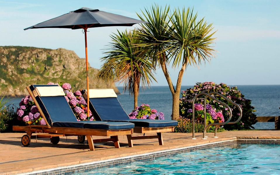 two sunloungers next to pool and palm trees overlooking the sea