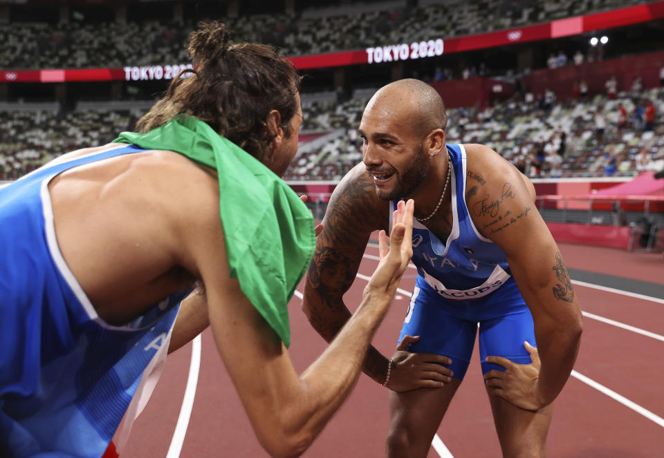 Lamont Marcell Jacobs of Italy is congratulated by teammate Gianmarco Tamberi after winning the final of the men's 100-meters at the 2020 Summer Olympics, Sunday, Aug. 1, 2021 in Tokyo, Japan. (Cameron Spencer/Pool Photo via AP)