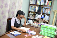 In this photo taken on Tuesday, Oct. 13, 2020, Dodeye Ewa, 16 year old study at the family library in Calabar, Nigeria. The third child is bothered by President Donald Trump's rhetoric and his policies toward international students, most recently one announced Friday that limits their stays in the U.S. to two or four years with uncertainty about whether their visas will be extended. (AP Photo/Daniel H Williams )