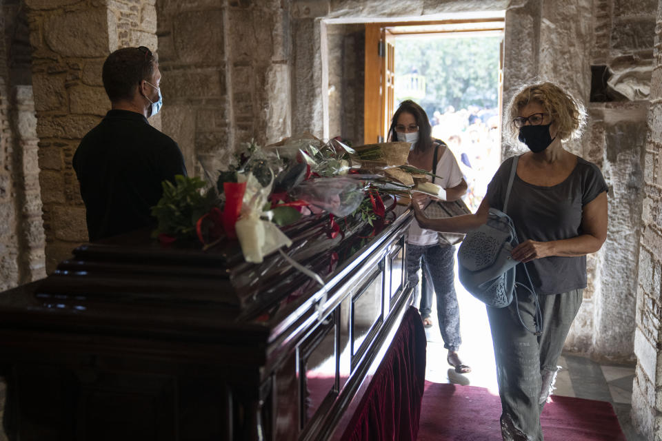 Women pay their final respects to the late composer Mikis Theodorakis, in Athens, on Monday Sept. 6, 2021. Hundreds of people have gathered outside Athens Cathedral where Greek composer and politician Mikis Theodorakis is to lie in state in a chapel of the cathedral for three days ahead of his burial on the southern island of Crete. (AP Photo/Petros Giannakouris)