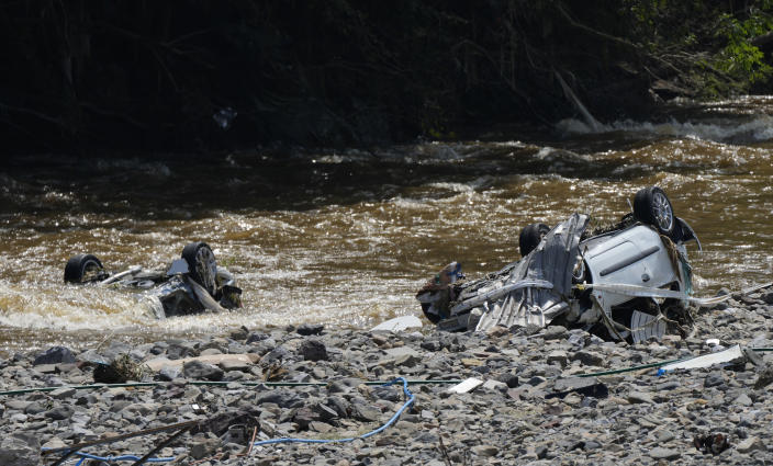 Damaged cars lay in riverbed after flooding in Drolenval, Belgium, Saturday, July 17, 2021. Uncontrollable water destroyed several towns, leaving tons of debris in its wake in one of the most violent natural disasters to hit Belgium in a century. (AP Photo/Virginia Mayo)