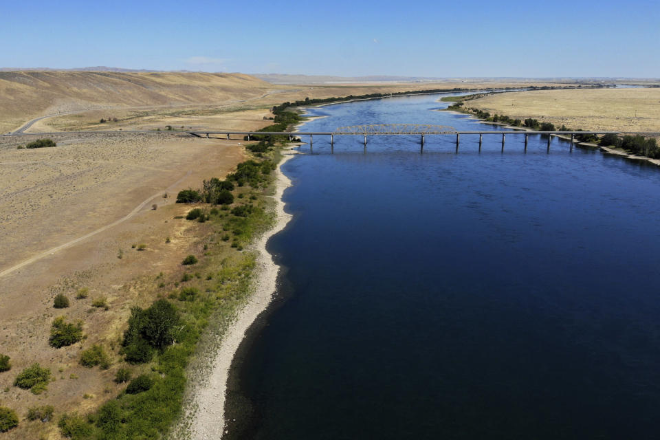 FILE - In this Aug. 14, 2019 photo, the Columbia River flows under the Vernita Bridge and past the Hanford Reach National Monument, left, and the Hanford Nuclear Reservation, right beyond the bridge, near Richland, Wash. The location is featured in a collection of mini-essays by American writers published online by the Frommer's guidebook company about places they believe helped shape and define America. (AP Photo/Elaine Thompson, File)