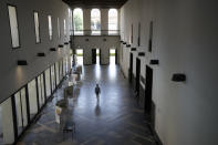 A person walks along a hallway of Milan's Statale University, northern Italy, Monday, June 21, 2021. Backed by 261 billion euros from the EU and Italian government, the country's recovery plan calls for a top-to-bottom shakeup of a major industrial economy long hampered by red tape, a fear of change, and bureaucratic and educational inertia. Leading the charge is Premier Mario Draghi, the former head of the European Central Bank, who was tapped as head of a national unity government specifically for his economic expertise and institutional knowledge both in Italy and the EU. A key target is keeping more young Italians from taking their know-how abroad, a perennial issue in Italy, which has one of the lowest rates of university graduates in Europe and one of the largest brain drains. (AP Photo/Antonio Calanni)