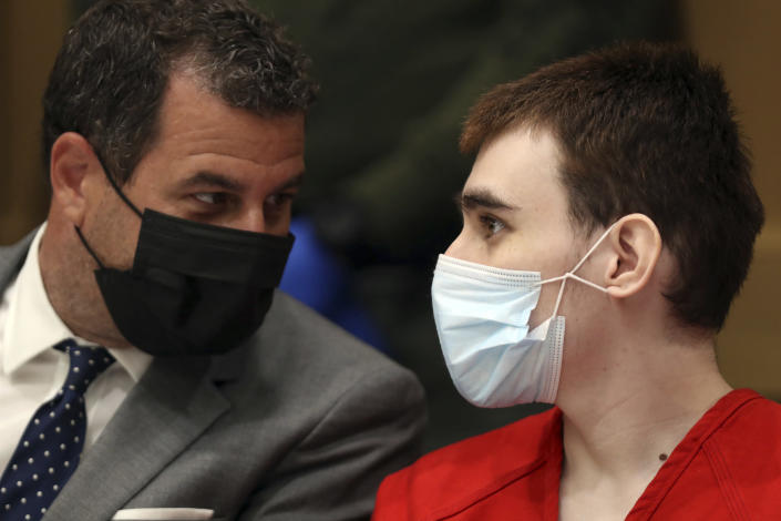Parkland school shooter Nikolas Cruz speaks to defense attorney Gabe Ermine during a pre-trial hearing at the Broward County Courthouse in Fort Lauderdale, Fla., Wednesday, July 14, 2021, on four criminal counts stemming from his alleged attack on a Broward jail guard in November 2018. Cruz is accused of punching Sgt. Ray Beltran, wrestling him to the ground and taking his stun gun. (Amy Beth Bennett/South Florida Sun-Sentinel via AP, Pool)