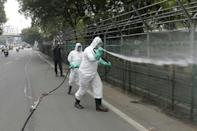 Workers disinfect a fence in Hyderabad, India, where cases are surging