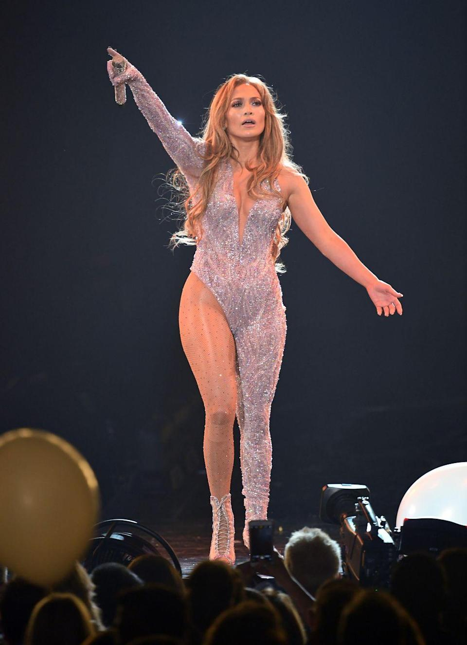 <p>Jenny from the block performs onstage in California during her It's My Party Tour in an asymmetrical glitter jumpsuit. Seriously, IDK how she does it, but she looks amazing wearing one pant leg?!</p>