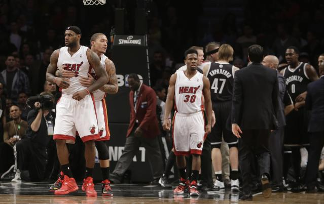 Miami Heat's Michael Beasley (8) walks LeBron James (6) away from an altercation during the second half of an NBA basketball game against the Brooklyn Nets, Friday, Jan. 10, 2014, in New York. The Nets won the game 104-95. (AP Photo/Frank Franklin II)