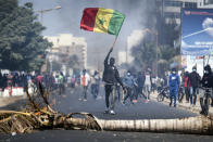 A demonstrator waves a Senegalese national flag during protests in support of main opposition leader and former presidential candidate Ousmane Sonko in Dakar, Senegal, Wednesday, March 3, 2021. Sonko was arrested Wednesday on charges of disturbing the public order after hundreds of his supporters clashed with police while he was heading to the court to face rape charges. (AP Photo/Leo Correa)