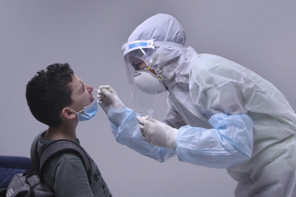 A healthcare worker takes a swab sample from a passenger who arrived at the Rafik Hariri International Airport in Beirut, Lebanon, Wednesday, July 1, 2020. Beirut's airport is partially reopening after a three-month shutdown and Lebanon's cash-strapped government is hoping that thousands of Lebanese expatriates will return for the summer, injecting dollars into the country's sinking economy. (AP Photo/Bilal Hussein)