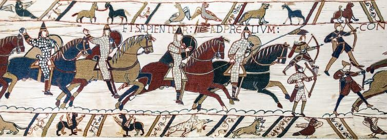 A scene from the Bayeux Tapestry depicting Norman knights on horseback, riding into battle.