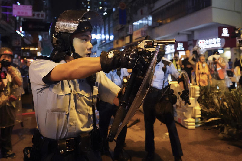 A policeman points a weapon during a protest in Hong Kong, Sunday, Aug. 25, 2019. Hong Kong police have rolled out water cannon trucks for the first time in this summer's pro-democracy protests. The two trucks moved forward with riot officers Sunday evening as they pushed protesters back along a street in the outlying Tsuen Wan district. (AP Photo/Vincent Yu)