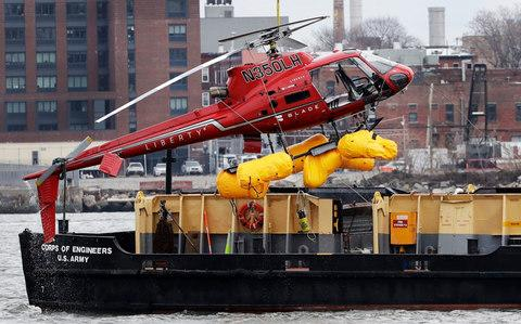 The helicopter is hoisted by crane from the East River onto a barge, Monday, March 12 - Credit: Mark Lennihan/AP