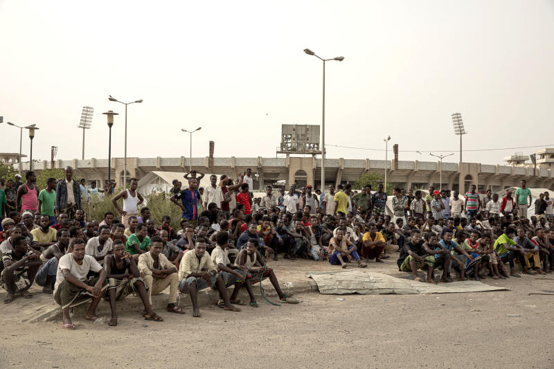 """In this July 21, 2019 photo, Ethiopian migrants take shelter in the """"22nd May Soccer Stadium,"""" destroyed by war, in Aden, Yemen. Over the summer, the stadium became a temporary refuge for thousands of migrants. At first, security forces used it to house migrants they captured in raids. Other migrants showed up voluntarily, hoping for shelter. The IOM distributed food at the stadium and arranged voluntary repatriation back home for some. The soccer pitch and stands became a field of tents, with clothes lines strung up around them. (AP Photo/Nariman El-Mofty)"""