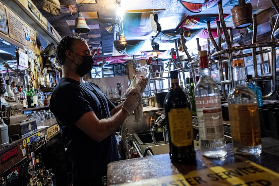A bartender cleans bottles of liquor inside a bar in San Francisco, California, U.S., on Thursday, May 6, 2021. San Francisco advanced into the least restrictive tier of California's color-coded reopening system Tuesday, allowing most businesses to expand capacity, bars to start serving indoors and large gatherings to resume inside and outside. (David Paul Morris/Bloomberg via Getty Images)
