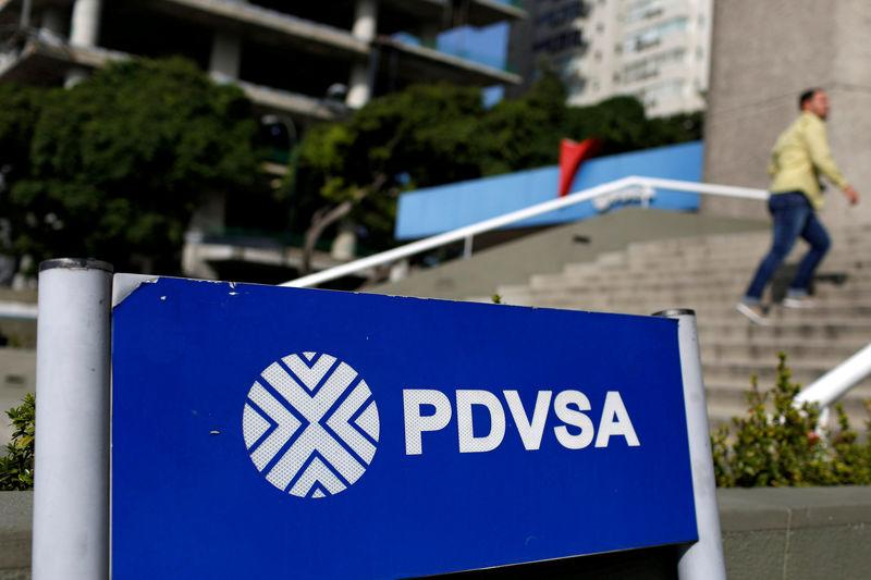 FILE PHOTO: A man walks past a gas station with the logos of the Venezuelan state oil company PDVSA in Caracas