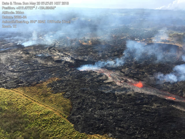 <p>In this Sunday, May 20, 2018, aerial photo provided by the U.S. Geological Survey, lava from the eastern channel of the Fissure 20 complex flows into a crack in the ground in Pahoa, Hawaii. (Photo: U.S. Geological Survey via AP) </p>