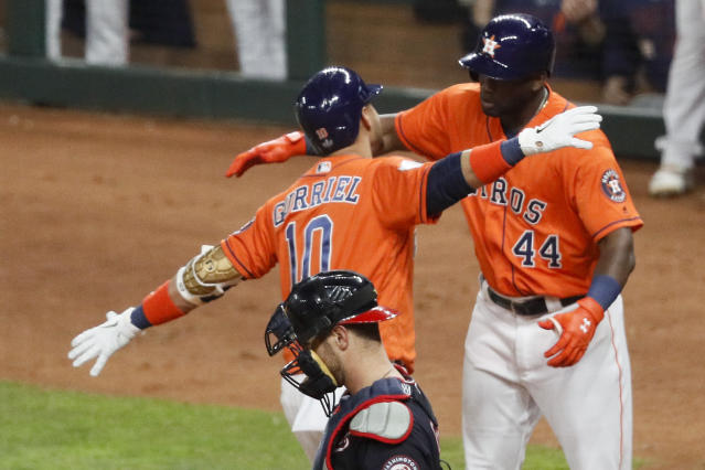 Houston Astros' Yuli Gurriel (10) celebrates with Yordan Alvarez past Washington Nationals catcher Yan Gomes after his home run during the second inning of Game 7 of the baseball World Series Wednesday, Oct. 30, 2019, in Houston. (AP Photo/Sue Ogrocki)