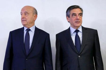 FILE PHOTO: Francois Fillon, former French prime minister, and Alain Juppe, current mayor of Bordeaux, stand together after the results in the second round for the French center-right presidential primary election in Paris, France