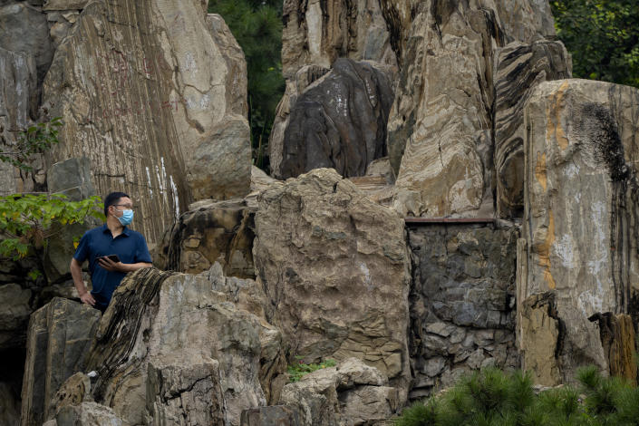 A man wearing a face mask to protect against COVID-19 stands amid a rock formation at a public park in Beijing, Thursday, Sept. 9, 2021. (AP Photo/Mark Schiefelbein)
