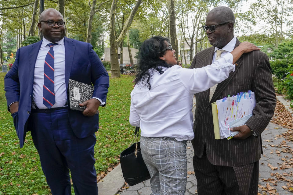 R. Kelly supporter Carlotte Woods, center, of Kentucky, hugs his attorney Deveraux Cannick, right, as he returns to Brooklyn Federal court after a lunch break in R&B star's trial, Thursday, Aug. 19, 2021, in New York. (AP Photo/Mary Altaffer)