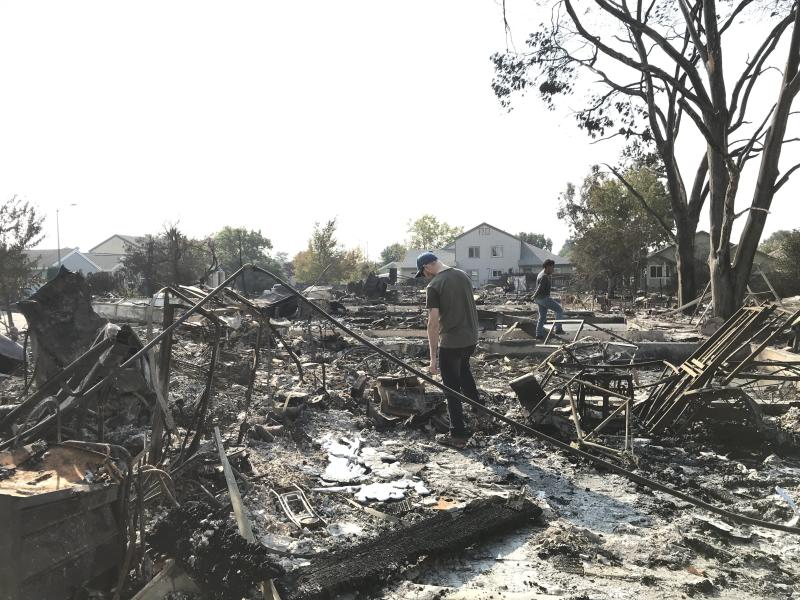 Maryanne Rahab (right) walks through the rubble of the house she had been renting in Coffey Park for over a year with her boyfriend, Sean Parsons (left). (Sarah Ruiz-Grossman/HuffPost)