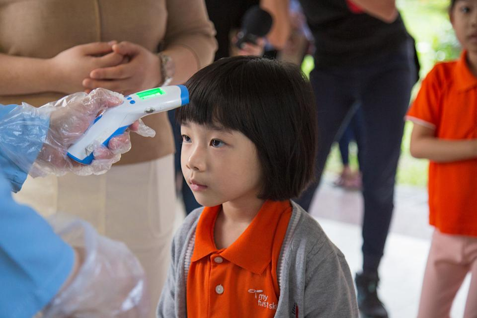 A pre-schooler gets her temperature tested at the My First Skool branch in Buangkok Crescent on Tuesday (28 January). (PHOTO: Dhany Osman / Yahoo News Singapore)