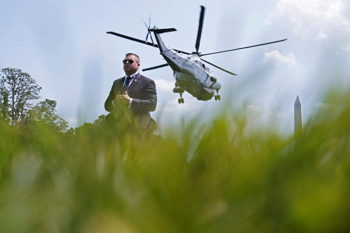 A member of the U.S. Secret Service stands by as Marine One, with President Joe Biden aboard, lifts off from the South Lawn of the White House in Washington, Friday, July 16, 2021. Biden is heading to Camp David for the weekend. (AP Photo/Susan Walsh)