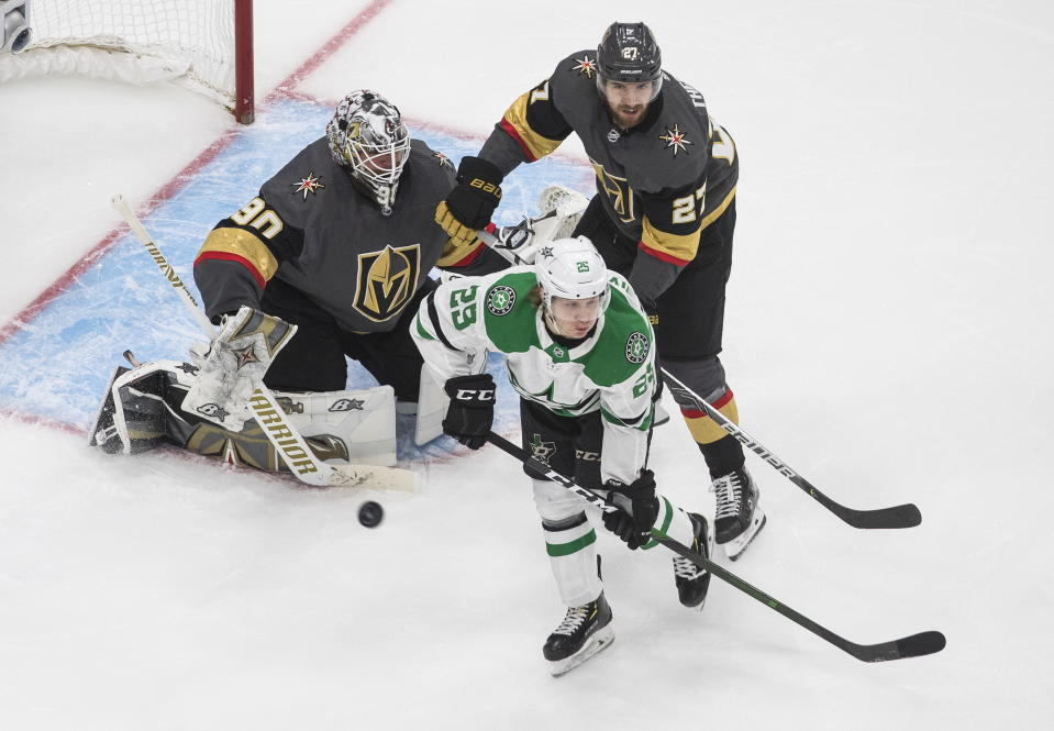 Dallas Stars' Joel Kiviranta (25) and Vegas Golden Knights' Shea Theodore (27) look for a rebound from Golden Knights goalie Robin Lehner (90) during third-period NHL Western Conference final playoff game action in Edmonton, Alberta, Monday, Sept. 14, 2020. (Jason Franson/The Canadian Press via AP)