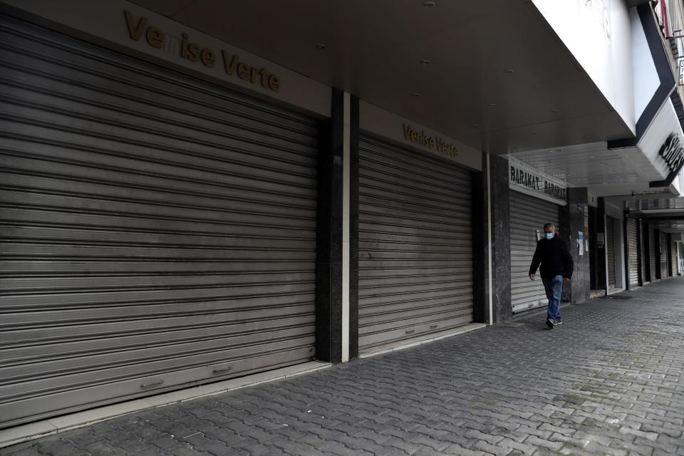 A man walks past closed shops as the country starts a new lockdown, in Beirut, Lebanon, Thursday, Jan. 14, 2021. Lebanese authorities began enforcing an 11-day nationwide shutdown and round the clock curfew Thursday, hoping to limit the spread of coronavirus infections spinning out of control after the holiday period. (AP Photo/Bilal Hussein)